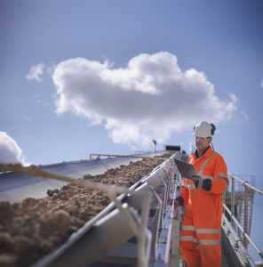 Worker inspecting stone screening and crushing machine in quarry